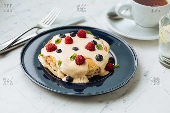 Pancakes topped with berries and served with tea