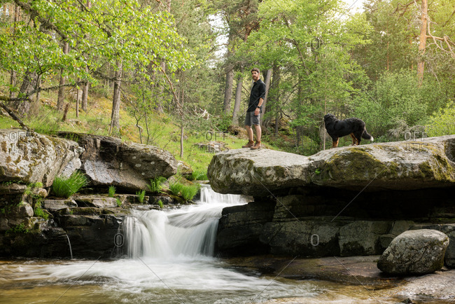Young man enjoys rest at the waterfall after adventure with his dog