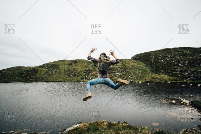 Back view of man with backpack jumping above ground on background of lake and mountains