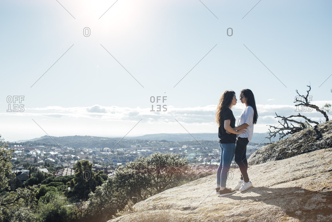 Young alternative couple is about to kiss standing on a hill in sunny day. Horizontal outdoors shot