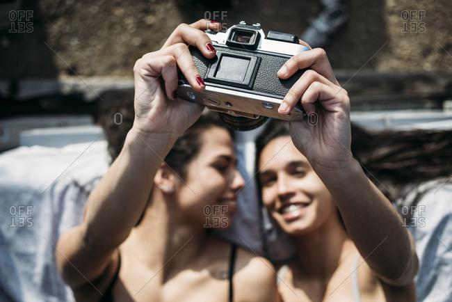 Happy alternative couple self-shooting on photo camera. Horizontal outdoors shot