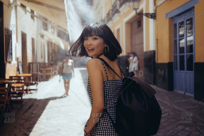 Young lovely model with backpack looking at camera over shoulder while walking on street