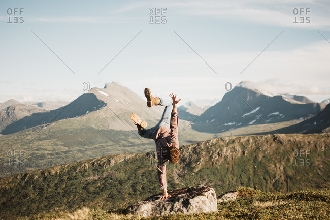 Anonymous man performing handstand on rock with background of mountains