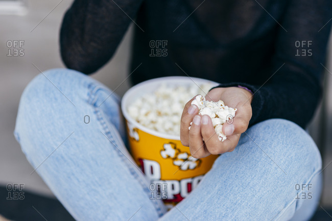 Faceless teenager sitting with bucket of popcorn and pile of it in hand