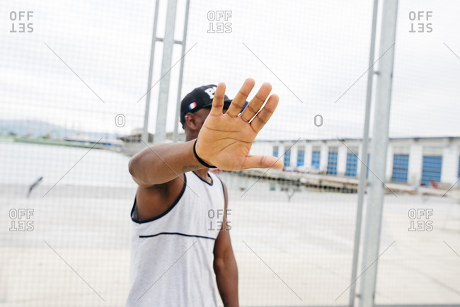 Anonymous black man in sportswear outstretching hand covering face on sports ground