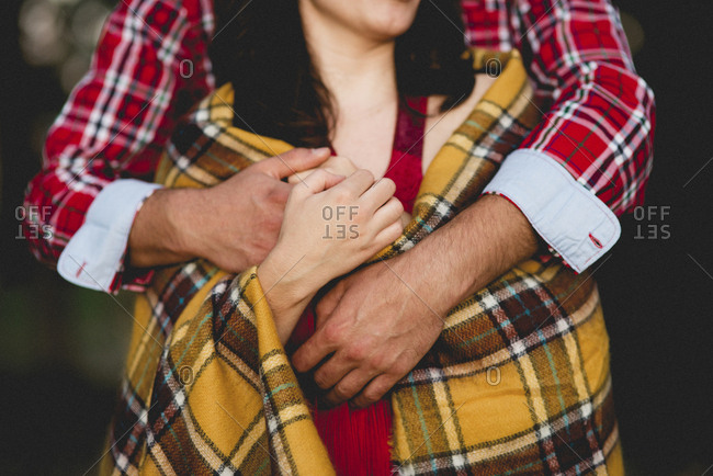 Unrecognizable man covering girlfriend with plaid and embracing her