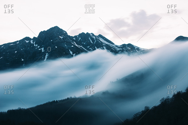 Landscape of fog on slope of rocky mountains with white fog above.