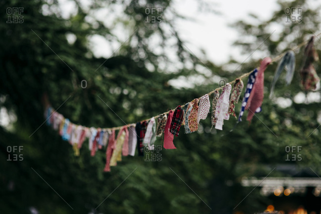 Long rope with colorful shreds making garland hanging among trees on festive