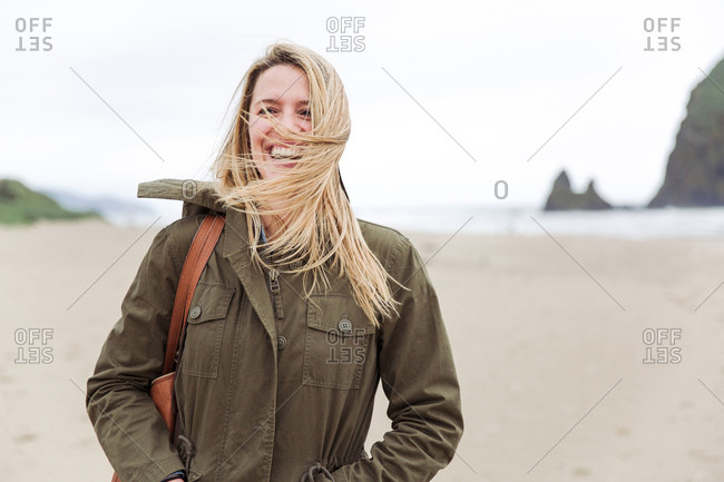 Blonde woman standing on coast of Cannon Beach, Oregon on a windy day
