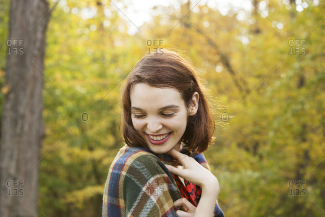 Beautiful young woman smiling against trees in forest during autumn