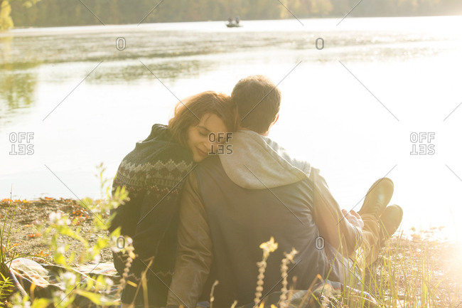 Beautiful young woman resting her head on man's shoulder while sitting by lake