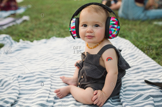 Baby with ear protectors at outdoor concert