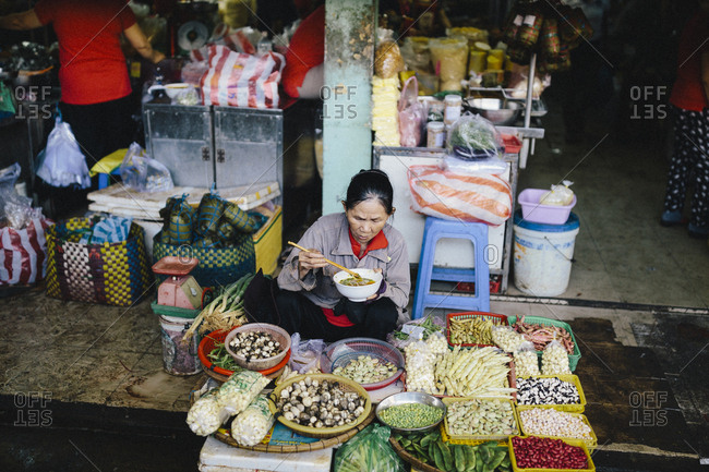 March 30, 2017: A vegetable seller pauses for a bowl of breakfast noodles at Con Market in Danang, Vietnam.