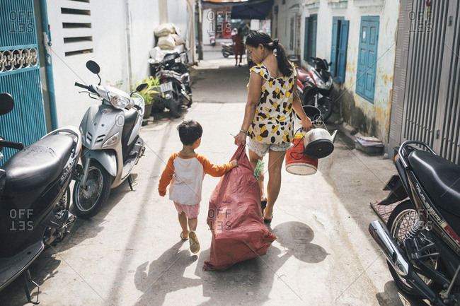 March 30, 2017: A young girl helps her mother carry kitchen equipment through an alleyway in Danang, Vietnam.