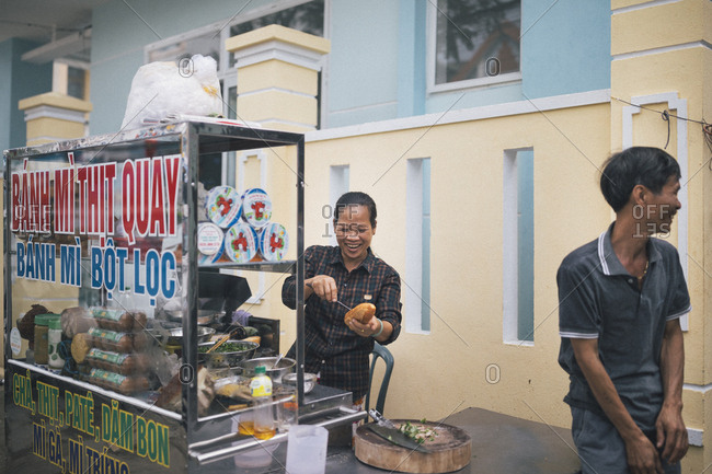 March 30, 2017: A woman makes a Banh Mi sandwich with pork and herbs street side in Danang, Vietnam.