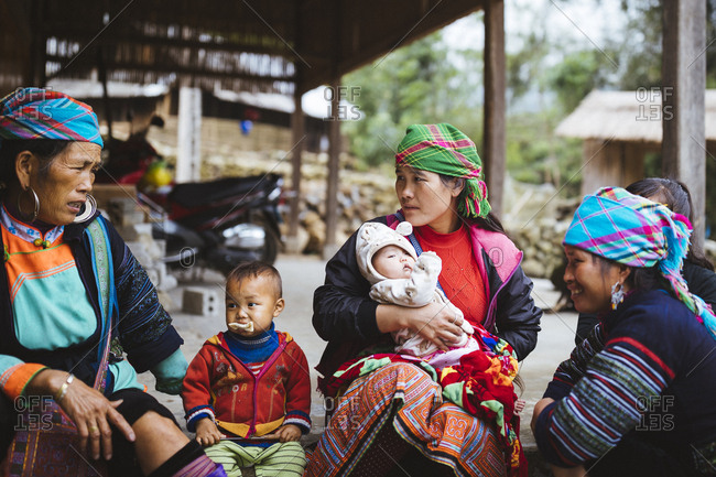 April 25, 2017: Hmong women and children sit around outside the Waterfall Homestay in Giang Ta Chai village, about 18km from Sapa in northern Vietnam.