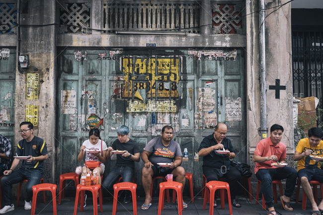 June 1, 2017: Crowds of people eating food on the streets of the Old Town in front of an old shophouse in Bangkok, Thailand.
