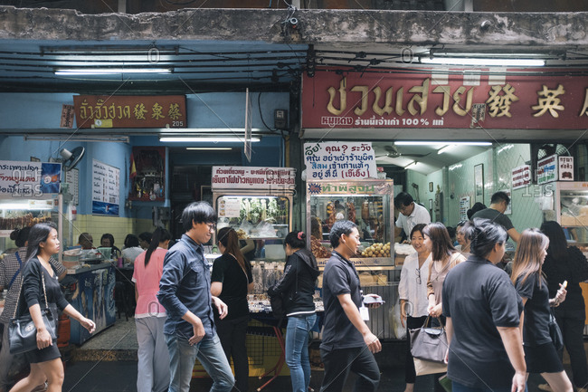 June 1, 2017: Small shophouse restaurants selling variations on pork and noodles along Silom Rd in downtown Bangkok, Thailand.