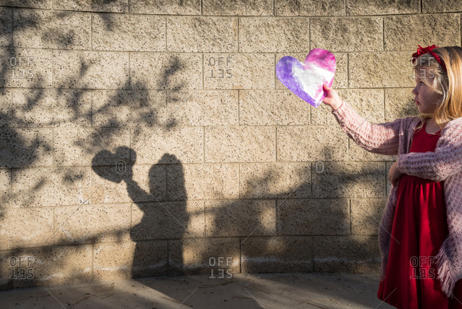 Young girl casting a shadow on wall with paper heart
