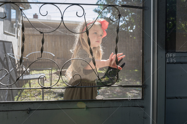 Young girl with her hand on screen door