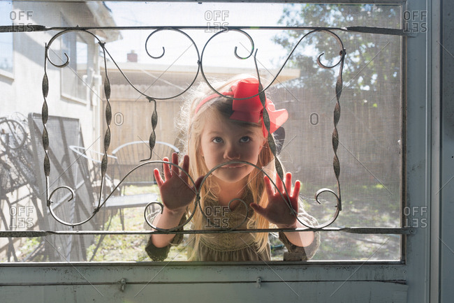 Girl pressing her face on a screen door