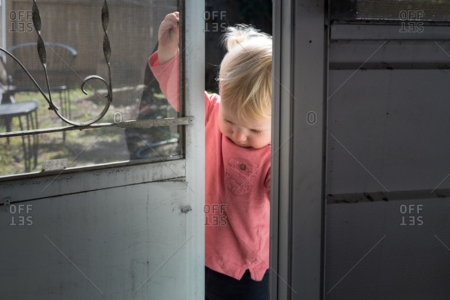 Toddler girl opening a screen door