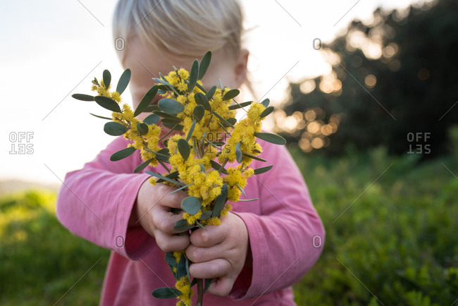 Toddler girl with bunch of yellow flowers