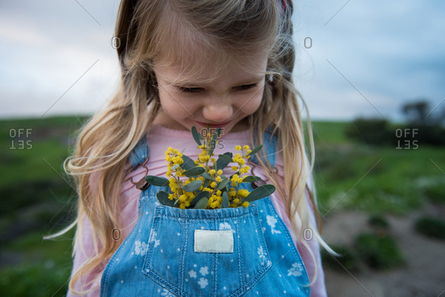 Young girl with flowers in the bib pocket of her overalls