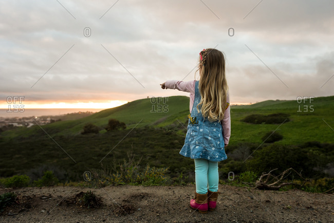 Back view of little girl pointing toward sunset