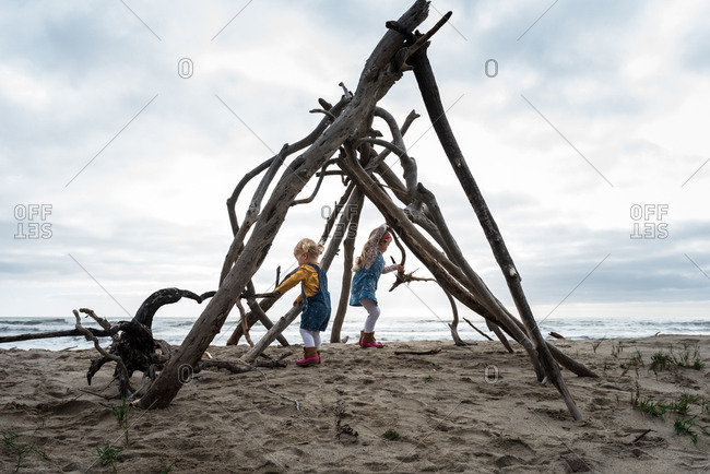 Children playing in driftwood structure on beach