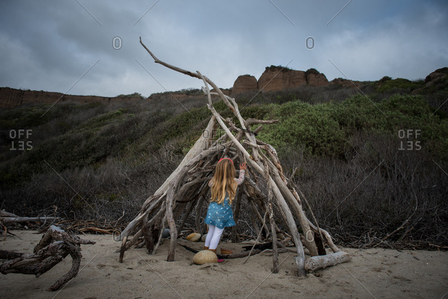 Girl playing in driftwood fort on beach