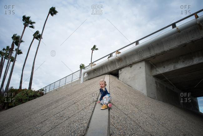 Toddler girl climbing concrete embankment