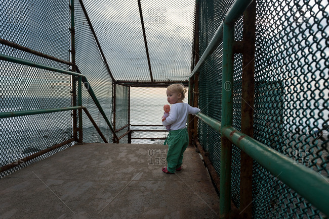 Toddler girl carrying baby doll over stairway to beach