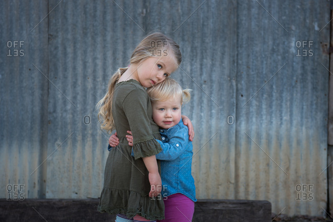 Portrait of two affectionate young sisters against metal shed