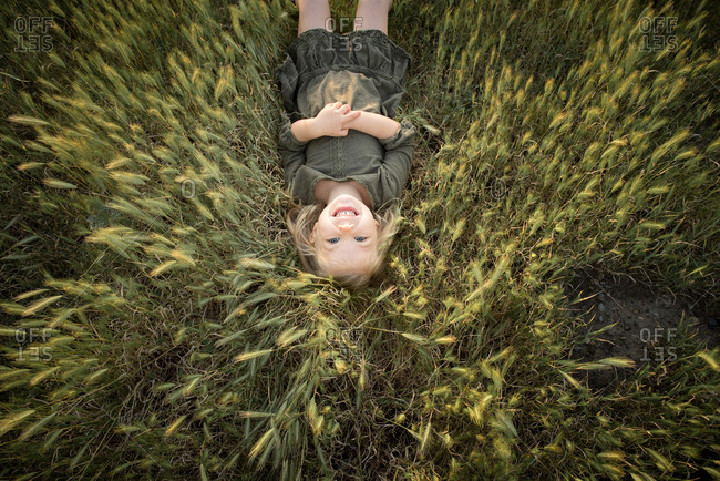 Overhead view of happy young girl lying in field of tall grass