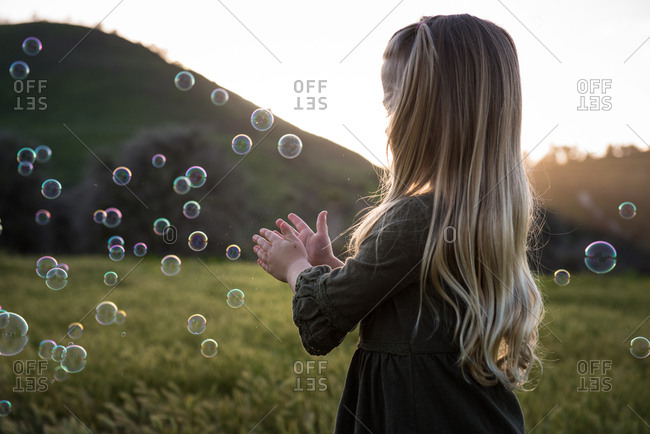 Young girl playing with bubbles at dusk