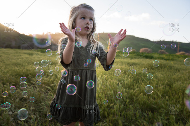Little girl popping bubbles in field at dusk