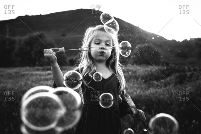 Girl blowing bubbles in meadow at dusk