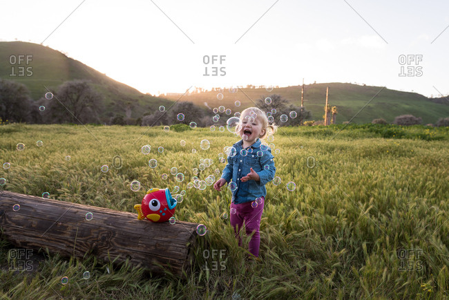 Happy toddler girl playing with bubble blower at dusk