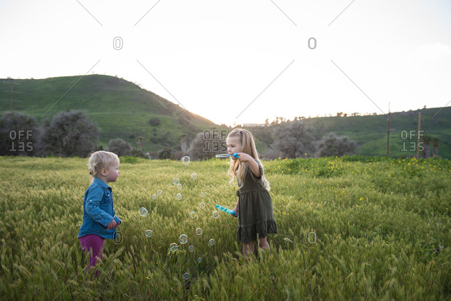 Two young sisters playing with bubbles in meadow