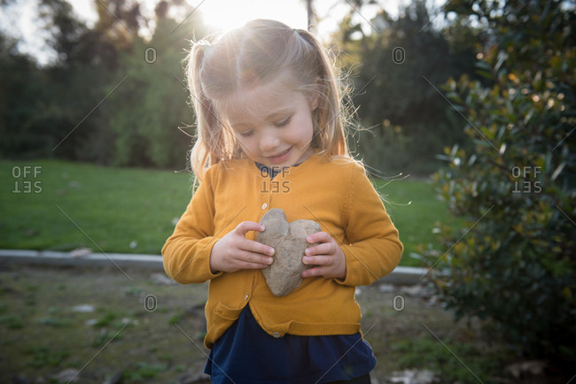 Young girl holding a heart shaped rock