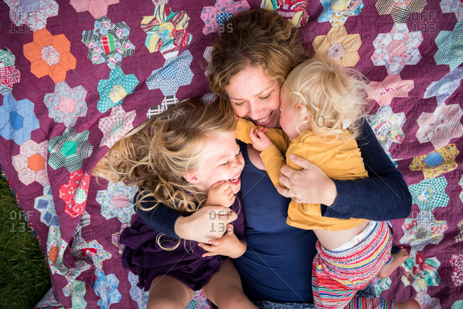 Overhead portrait of affectionate mother with two young daughters lying on quilt