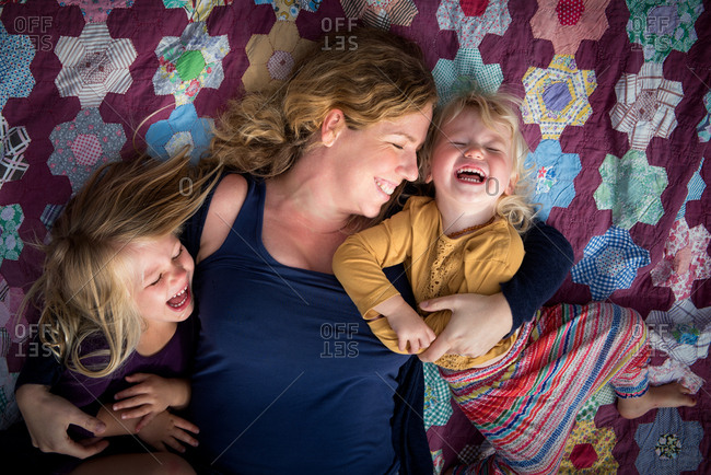 Portrait of mother with happy young daughters on quilt