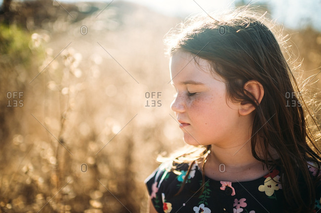 Girl with eyes closed in field
