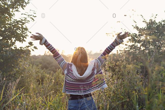 Woman raising arms in a prairie