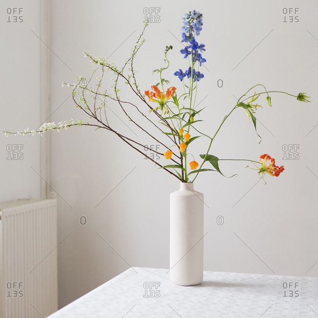 Blue and orange flowers arranged in a modern vase in a minimalist interior