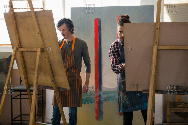 Male artists painting on easel in art class