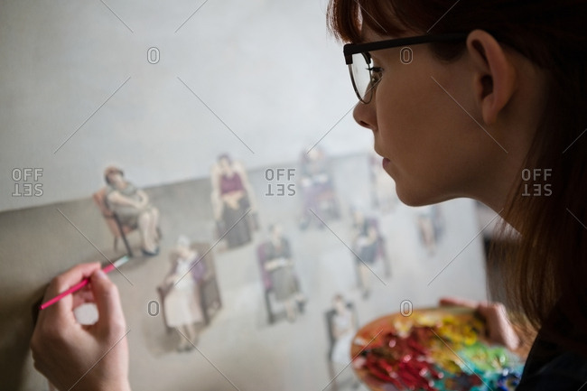 Close up of female artist painting on canvas in art class