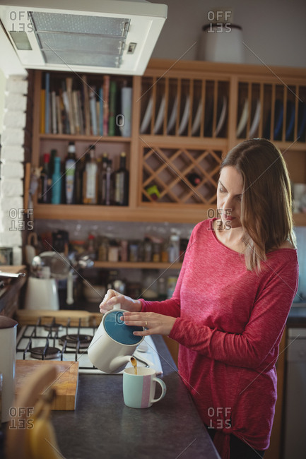 Woman pouring tea from teapot into mug at home
