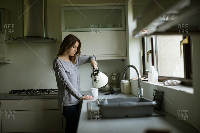 Woman pouring tea in cup while standing in kitchen